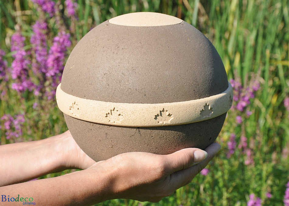 De van organisch compost, zand en mineralen vervaardigde biologisch afbreekbare eco-urn Geos, op handen gedragen.