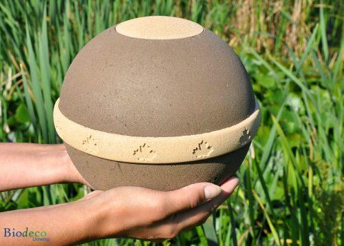 Biologisch afbreekbare eco-urn Geos, de uit plantaardige materialen vervaardigd, op handen gedragen. Asbijzetting in de aarde