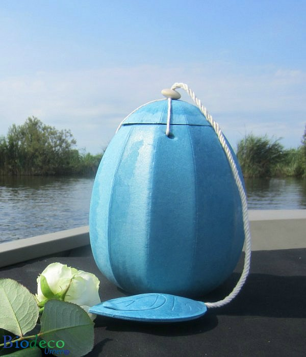 De zee-urn Beyond in het lichtblauw, opgesteld op het voordek van een boot, voor een asbijzetting in het water