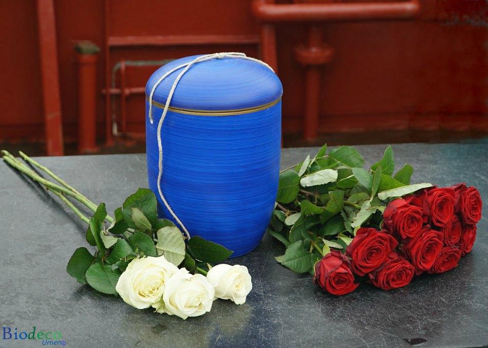 De biologisch afbreekbare zee-urn Oceaanblauw, opgesteld met bloemen op het dek van een schip