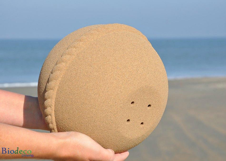 De onderkant van de Sand Round zee-urn met gaatjes, voor het verplaatsen van lucht in de urn tijdens een asbijzetting