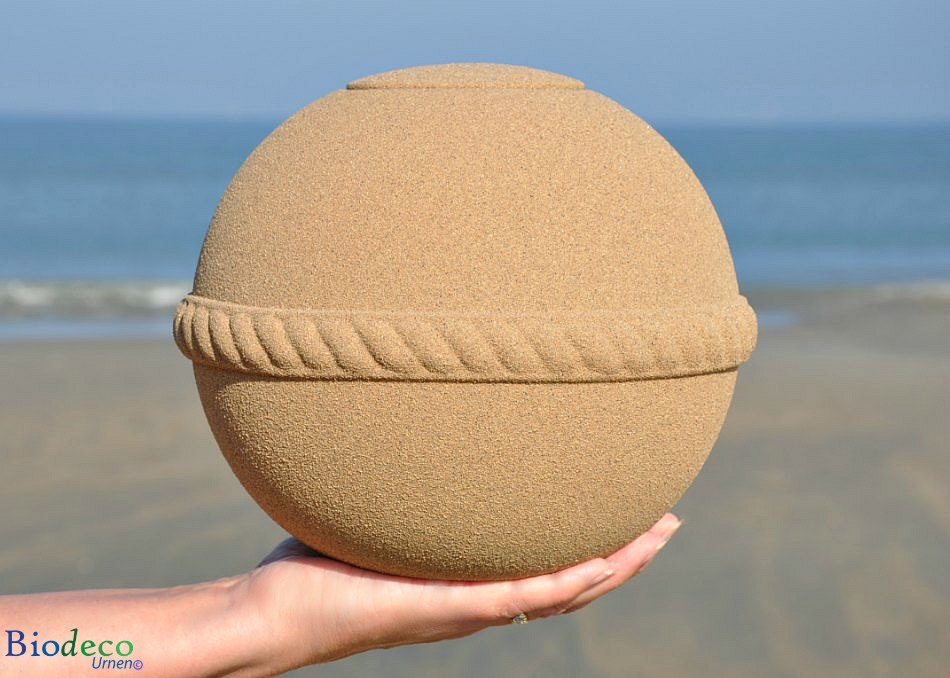 De Sand Round zee-urn in de hand, op het strand van Scheveningen met de Noordzee op de achtergrond