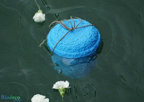 De zee-urn Zeeblauw, bijgezet in de Noordzee voor de kust van Hoek van Holland, met bloemen als laatste groet
