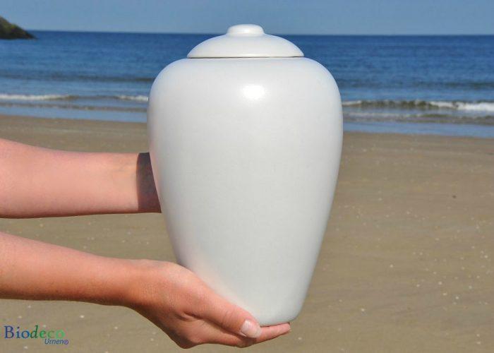 Bio-urn Classic Parel, biologisch afbreekbare urn in handen gedragen, op het strand voor de Noordzee
