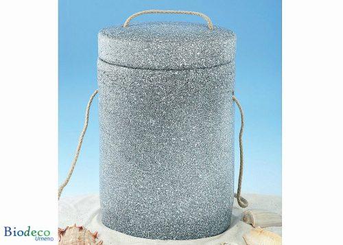 De biologisch afbreekbare zee-urn Basaltlava in het zand, met touw voor een asbijzetting in het water