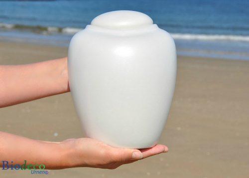 Zee-urn Ocean Parel, biologisch afbreekbare urn in handen gedragen op het strand van Scheveningen