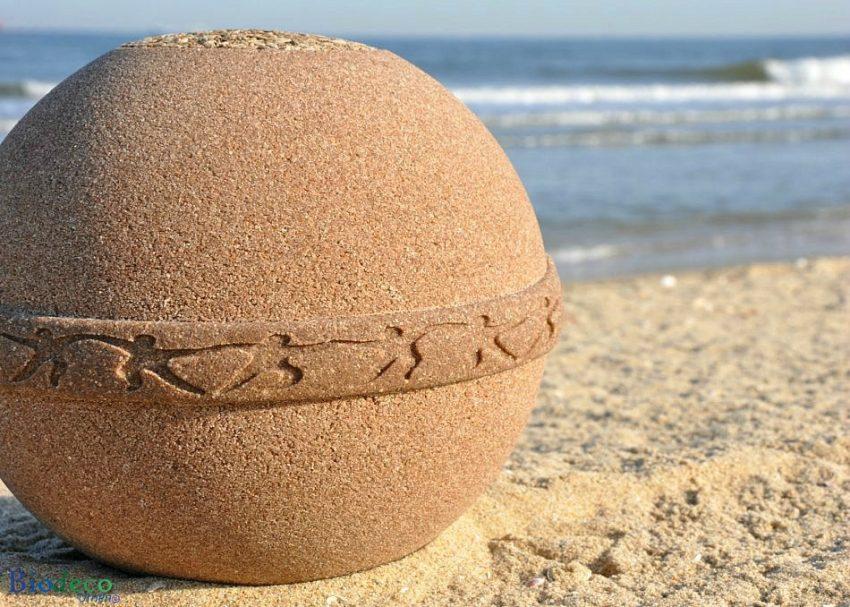 De eco-urn Samsara Zand op het strand met de Noordzee op de achtergrond, van Goudzand