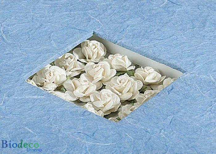 Detail van de biologisch afbreekbare urn Bloemen Boeket, ingelegd met witte papieren roosjes, voor een asbijzetting in de aarde