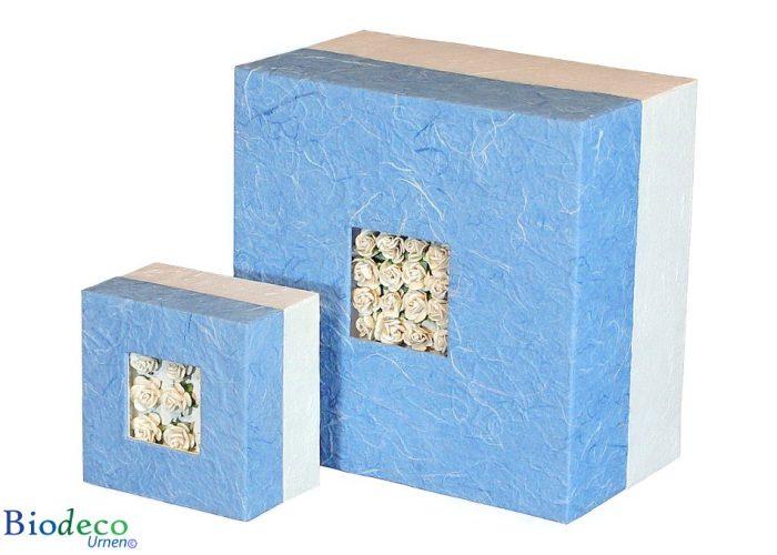 De biologisch afbreekbare urn Bloemen Boeket, ingelegd met witte papieren roosjes, voor een asbijzetting in de aarde