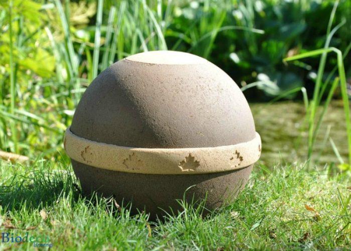 De biologisch afbreekbare eco-urn Geos, vervaardigd van gehard organisch compost, zand en mineralen, in het gras.